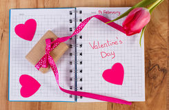 Valentines Day written in notebook, fresh tulip, wrapped gift and hearts, decoration for Valentines Royalty Free Stock Images