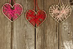 Valentines Day yarn hearts top border on rustic wood Royalty Free Stock Images
