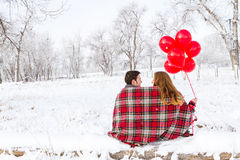 Valentines Day. Young couple at the picnic on the Valentines Day in a snowy park Stock Photos