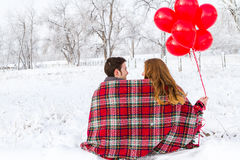 Valentines Day. Young couple at the picnic on the Valentines Day in a snowy park Royalty Free Stock Image