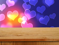 Valentines Design. Empty wooden deck table over hearts motif. Re Stock Photos
