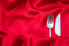 Valentines dinner, Cutlery, fork and knife on red satin background, copy space, top view stock images