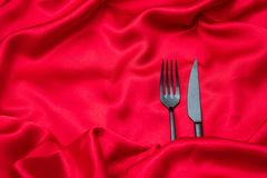 Valentines dinner, Cutlery, fork and knife on red satin background, copy space, top view stock image