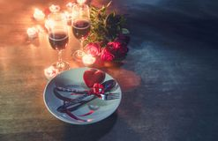 Valentines dinner romantic love concept Romantic table setting decorated with Red heart fork spoon on plate and couple champagne royalty free stock image