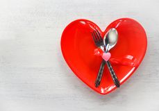 Valentines dinner romantic love food and love cooking concept Romantic table setting decorated with fork spoon in red heart plate stock image