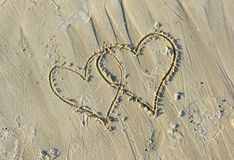 Valentines Drawn on Sandy Beach. A couple of valentines symbols drawn on wet sand of a beach Royalty Free Stock Photos