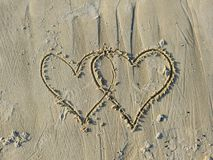 Valentines Drawn on Sandy Beach. A couple of valentines drawn on wet sand of a beach Royalty Free Stock Photography