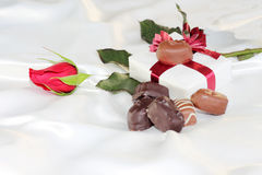 Valentines Gift. With a rose and gourmet chocolate laying on white satin Royalty Free Stock Image