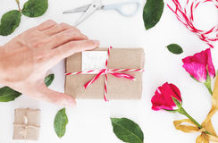 Valentines gift preparation, hand holding parcel gift box with roses and leaves, on white table Stock Image