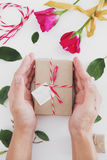 Valentines gift preparation, hand holding parcel gift box with roses and leaves, on white table Royalty Free Stock Images