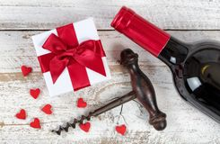 Red Wine for Valentines Day Gift. Valentines gift with red wine and corkscrew opener on rustic white wood in flat lay view Royalty Free Stock Image