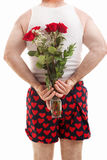 Valentines Guy in Underwear with Roses. Rear view of man in heart boxers holding a bouquet of flowers behind his back. White background royalty free stock images