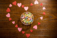 Valentines Heart and Sweet Heart Candies. In clear bowl and on wooden table royalty free stock image