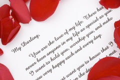 Valentines love letter. A romantic love letter with rose petals for Valentines day Stock Photo