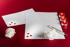 Valentines love letter writing setup, with envelope, paper, red background, candles and fire, flame and tissues. stock images