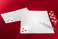 Valentines love letter writing setup, with envelope, paper, red hearts and candles with fire and flame on a red background. Stock Photo