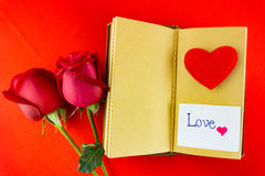 Valentines notebook with message card on red background Image of Royalty Free Stock Photography