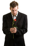 Valentines Portrait. A young man with a single red rose royalty free stock photo