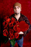 Valentines Portrait. A young man with a heart-shaped box of chocolates and a dozen red roses stock image