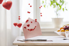Valentines_Post. Open pink envelope on table with hearts flying out Stock Photography