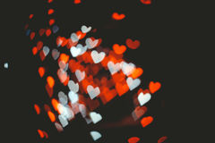 Valentines style defocused lights background. Red and white hearts bokeh in dark texture for use in graphic design. Valentines style defocused lights background Royalty Free Stock Photos