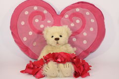 Valentines Teddy. Teddy bear with a big heart lying under a rose petal blanlet royalty free stock photo