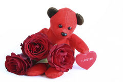 Valentines teddy bear. Red teddy bear with message on heart saying I love you and roses on red background Stock Images