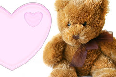 Valentines - Teddybear With Heart. A teddybear close-up with light pink heart. Shallow deph of field Royalty Free Stock Photo