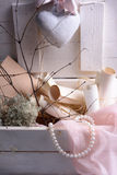 Valentines or wedding day still life of ceramic heart, pearls, pink laces and paper scrolls in vintage retro wooden box. Stock Images