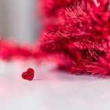 Valentinesday background with a heart and red glitter. Conceptual image with a glitter heart and red glitter unfocused in the background and copy space stock photography