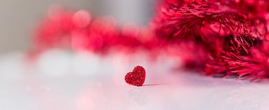 Valentinesday conceptual image. Red glitter heart banner with red tinsel unfocused background Stock Photo
