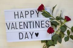 Valentinesday heureux écrit sur un lightbox avec des roses Image stock