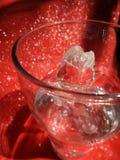 Valentinexponeringsglas steg i klart vatten på absolut röd bakgrund Royaltyfri Bild