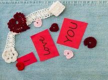 Valentinhälsningkort med den virkade rosa hjärtor och blomman, royaltyfri bild