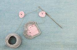 Valentinhälsningkort med virkade rosa hjärtor på grov bomullstvill royaltyfria bilder