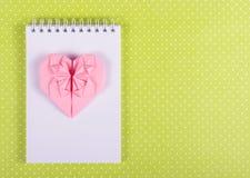 Valentinorigami av rosa färgpapper, öppen anteckningsbok med tomma sidor Arkivbild