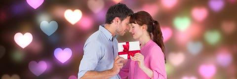 Valentinpar som ger gåvor med förälskelsehjärtabakgrund arkivfoto