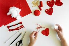 Valentins dag klädde med filt hantverk Kvinnahänder som syr röda hjärtor DIY Lekmanna- lägenhet Top beskådar arkivfoton