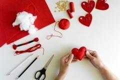 Valentins dag klädde med filt hantverk Kvinnahänder som syr röda hjärtor DIY Lekmanna- lägenhet Top beskådar arkivbilder