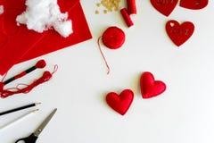 Valentins dag klädde med filt hantverk Kvinnahänder som syr röda hjärtor DIY Lekmanna- lägenhet Top beskådar royaltyfri foto