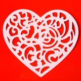 Valentinsgruß, der Herz auf dem roten Papierhintergrund schnitzt Lizenzfreies Stockbild