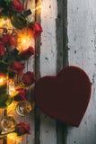 Valentinsgruß: Süßigkeits-Kasten auf hölzernem Hintergrund mit Rosen und Champagne Lizenzfreies Stockfoto