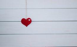 Valentinsgruß ` s Herz, das an der natürlichen Schnur hängt Hölzerner weißer Hintergrund Retro- Art Stockfotos