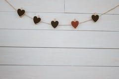 Valentinsgruß ` s Herzen hangin auf hölzernem weißem Hintergrund der natürlichen Schnur Retro- Art Stockfotografie