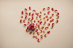 Valentinsgruß `s Karte Herzsymbol gemacht von getrockneten Rosen auf einem Weinlesehintergrund Draufsicht, flache Lage Konzept, P Stockfotografie