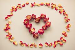 Valentinsgruß `s Karte Herzsymbol gemacht von getrockneten Rosen auf einem Weinlesehintergrund Draufsicht, flache Lage Konzept, P Stockbild