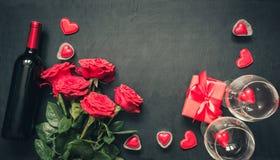 Valentinsgruß `s Karte Rote rosafarbene Blumen, Rotwein, Herzen und Geschenkbox auf Schwarzem Beschneidungspfad eingeschlossen Ko stockbilder