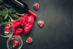 Valentinsgruß `s Karte Rote rosafarbene Blumen, Rotwein, Herzen und Geschenkbox auf Schwarzem Beschneidungspfad eingeschlossen Ko lizenzfreie stockfotografie