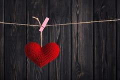 Valentinsgruß ` s rotes Herz auf Seil auf hölzernem Hintergrund Stockfotografie