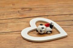 Valentinsgruß `s Tag Eine keramische Pandafigürchen mit einem roten Herzen Lizenzfreie Stockbilder